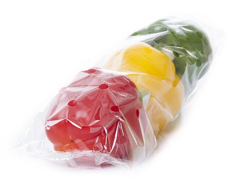 Un pimiento rojo, amarillo y verde puestos uno al lado del otro en una bolsa plástica de envoltura de flujo transparente