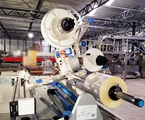 Una impresora de etiquetas conectada a una máquina de envoltura de flujo para una aplicación de etiquetas rápida y eficiente
