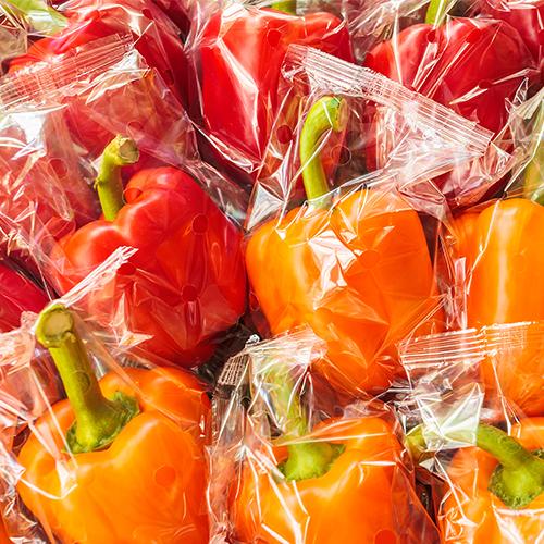 Pimientos rojos y naranjas individualmente envueltos en plástico puestos sobre en una pila