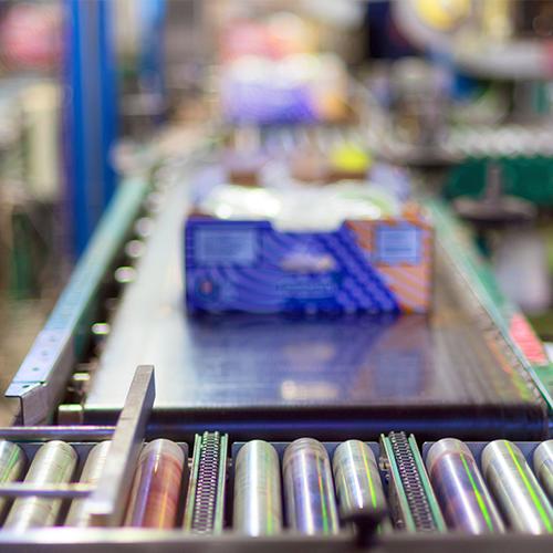 Cajas de productos de haciendo la transición entre un transportador de rodillos y un transportador de banda