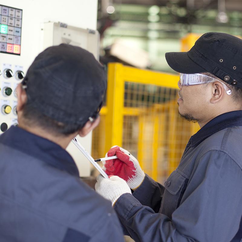 Dos técnicos de servicio miran un portapapeles al instalar una máquina de envasado