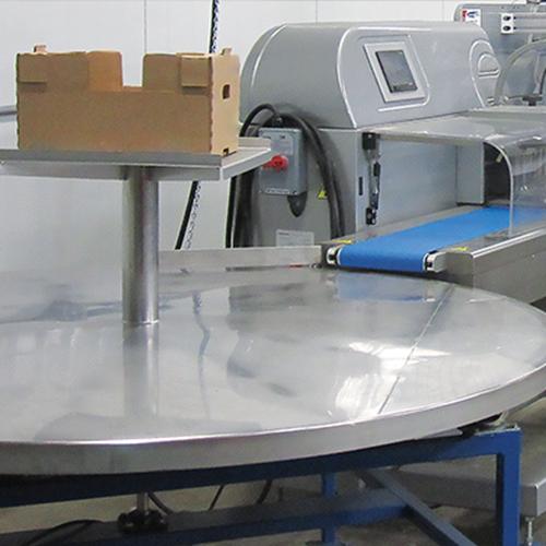 Una mesa de recolección giratoria se encuentra al final de una máquina de envoltura de flujo para organizar los productos