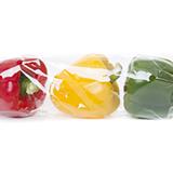 un pimiento rojo, amarillo y verde dentro de un paquete de envoltura de flujo transparente