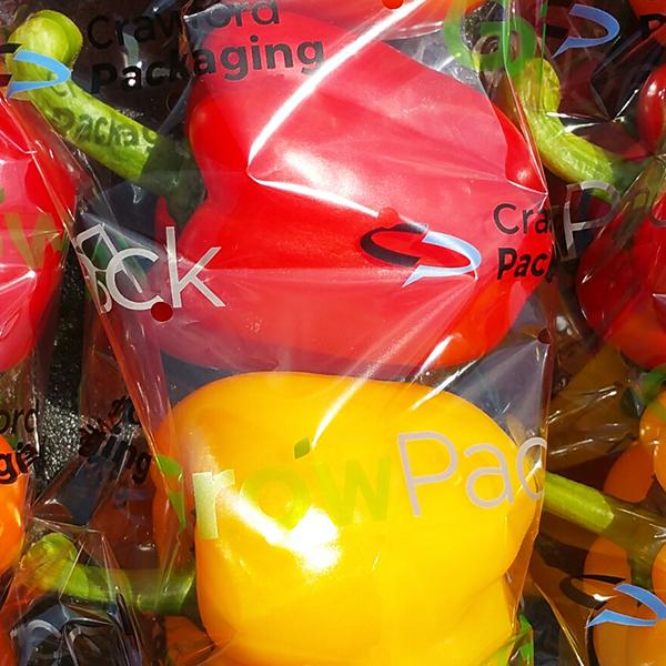 3 pimientos de varios colores dentro de un paquete de envoltura de flujo con el logotipo de Crawford Packaging