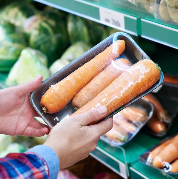 Un cliente en una tienda de comestibles mantiene una bandeja negra con tres zanahorias envueltas en envoltura retráctil