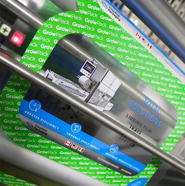 La película de sellado impresa con logotipos y la información del producto siendo aplicada a través de una máquina selladora de bandejas
