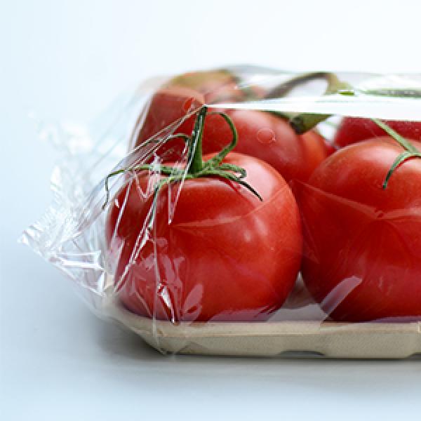 Varios tomates de color rojo brillante asentados en una bandeja de fibra envuelta en envases de envoltura de flujo