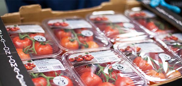 Una caja de cartón lleva varios paquetes de tomates de alta sellado con etiquetas impresas
